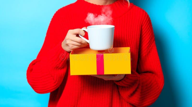 Fille dans le chandail rouge avec le boîte-cadeau et la tasse de café photos libres de droits