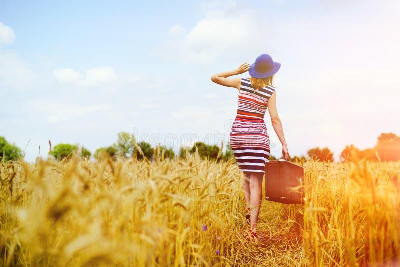 Fille dans le chapeau bleu marchant loin à la lumière du soleil d'or image libre de droits