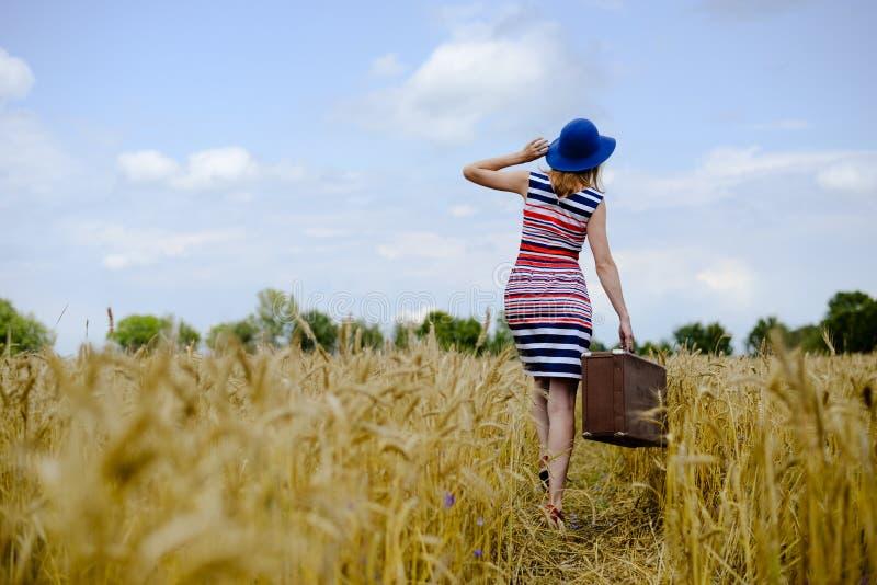 Fille dans le chapeau bleu marchant loin dans le blé d'or image stock
