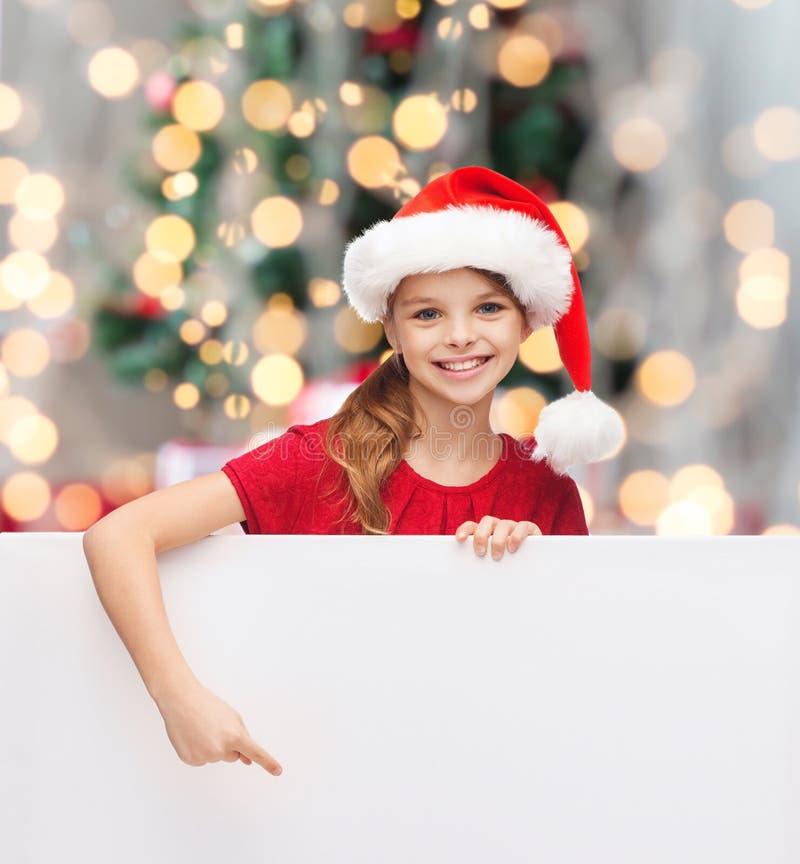 Fille dans le chapeau d'aide de Santa avec le conseil blanc vide photo stock