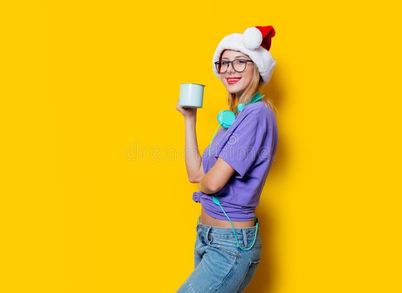 Fille dans le chapeau de Noël avec la tasse image stock