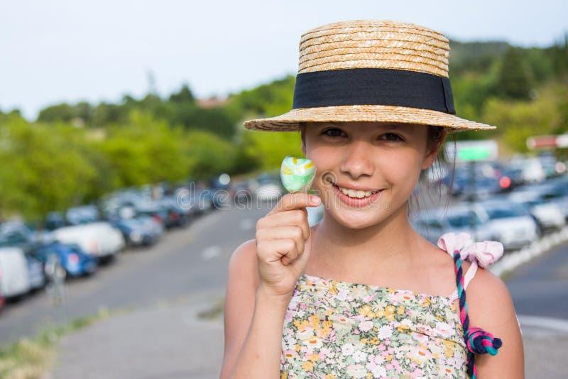 Fille dans le chapeau de paille et avec le lolipop photo stock