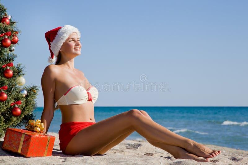 Fille dans le chapeau de Santa appréciant le soleil et la chaleur sur la station balnéaire pendant des vacances de Noël photographie stock libre de droits