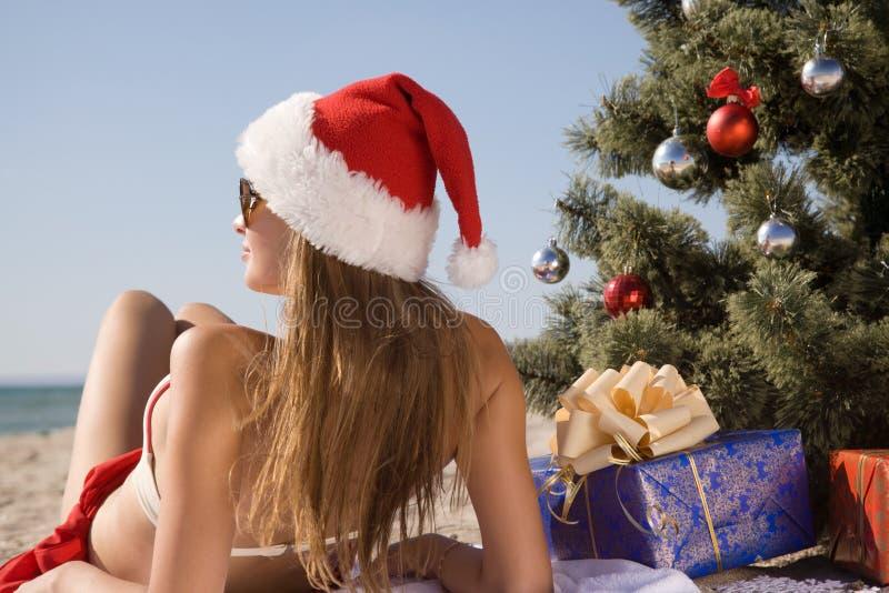 Fille dans le chapeau de Santa appréciant le soleil tout en se trouvant sur la plage près d'un arbre de Noël photos libres de droits