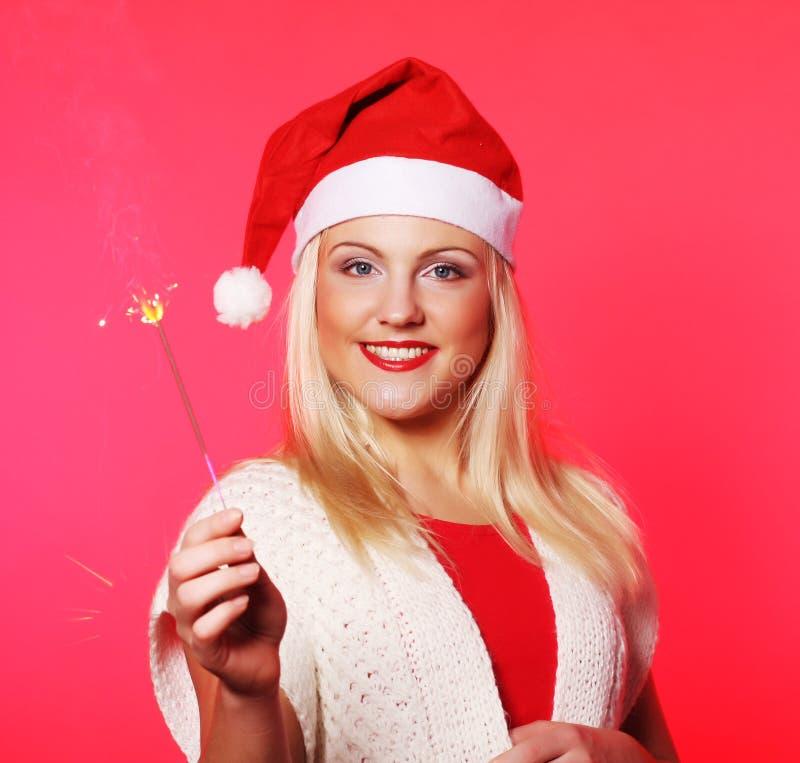Fille dans le chapeau de Santa tenant des cierges magiques images libres de droits