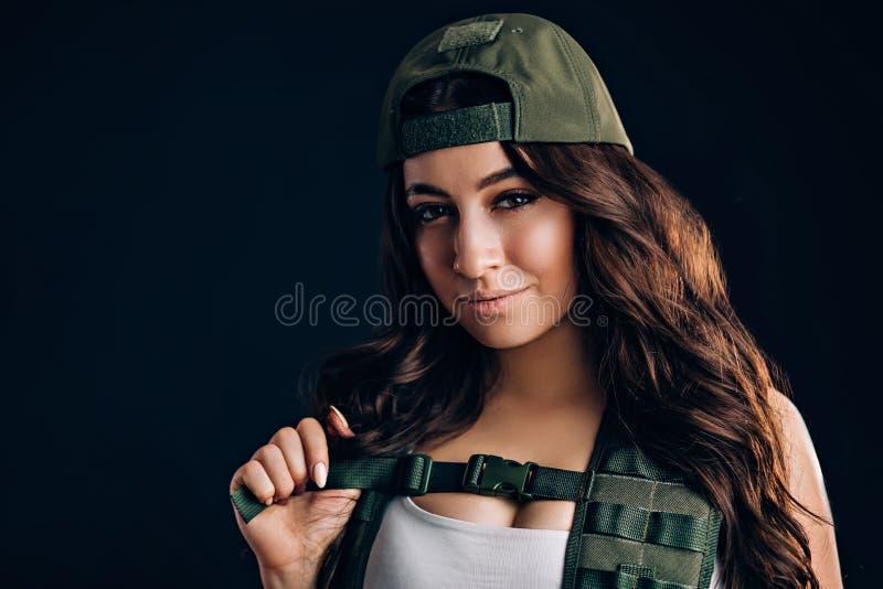 Fille dans le chapeau militaire souriant et regardant la caméra sur un fond noir image libre de droits