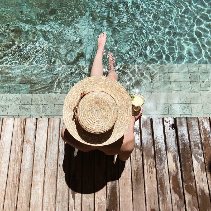 Fille dans le chapeau près de la piscine photo stock