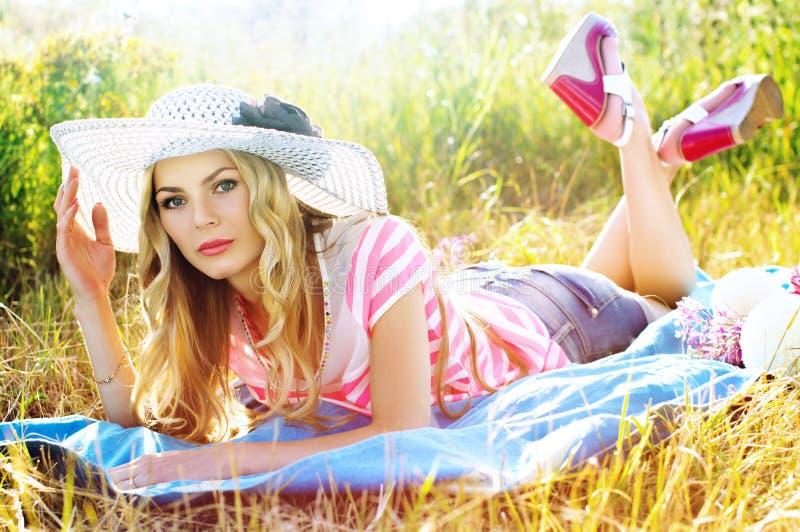 Fille dans le chapeau prenant un bain de soleil sur le soleil image libre de droits