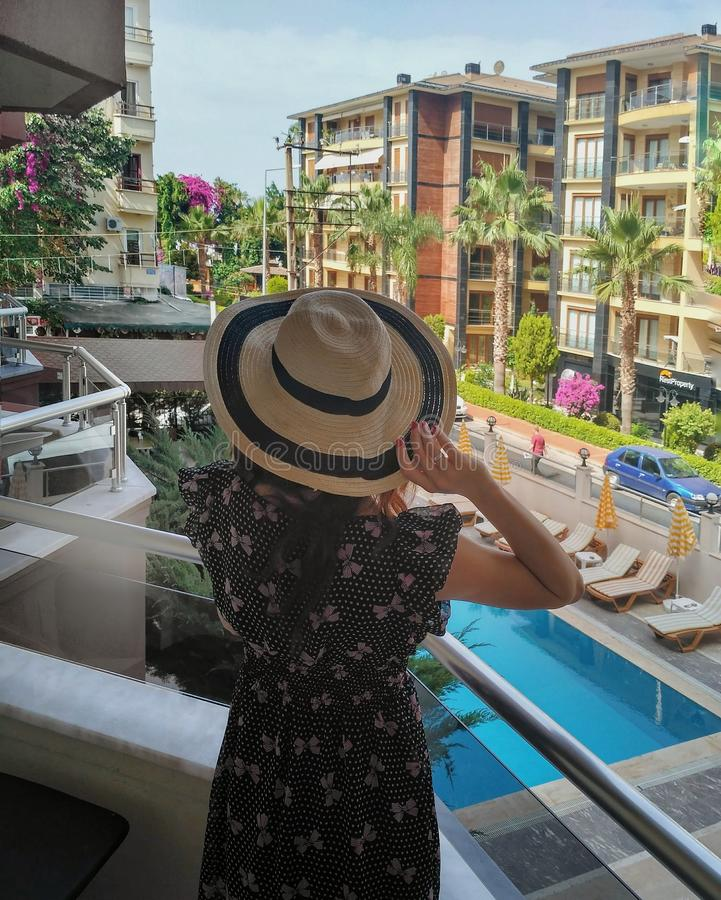 Fille dans le chapeau regardant sur la piscine de la chambre d'hôtel photos libres de droits