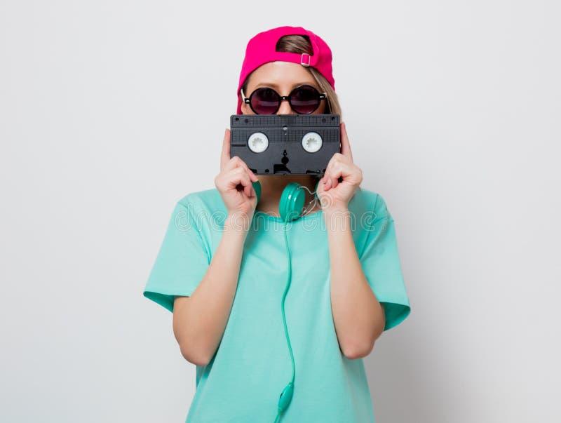 Fille dans le chapeau rose et le T-shirt bleu avec la cassette de VHS images libres de droits