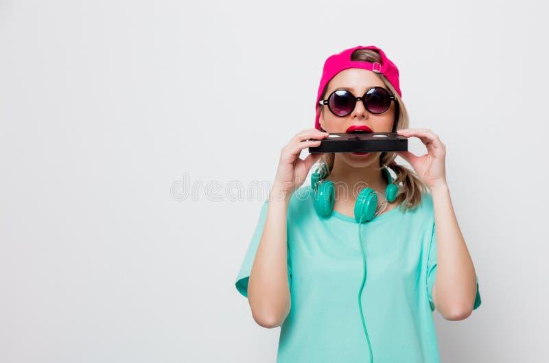 Fille dans le chapeau rose et le T-shirt bleu avec la cassette de VHS image stock
