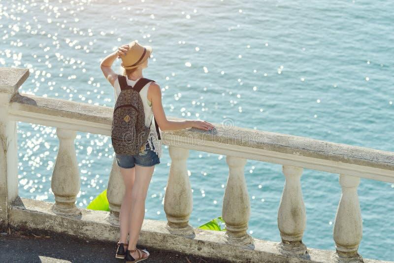 Fille dans le chapeau se tenant sur le balcon et regardant la mer dos photos stock