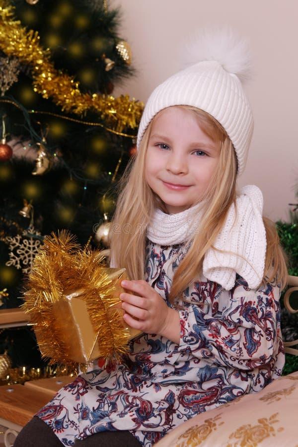 Fille dans le chapeau tricoté avec le cadeau d'or de Noël photographie stock