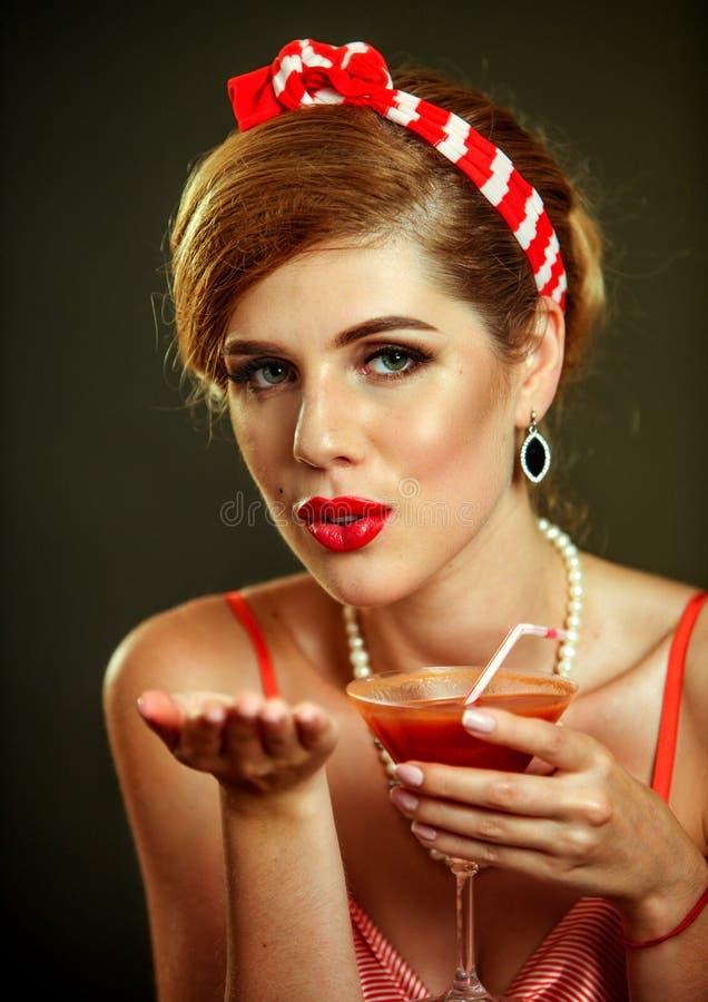 Fille dans le cocktail de martini de boissons de style de goupille- et le baiser de coup photo stock