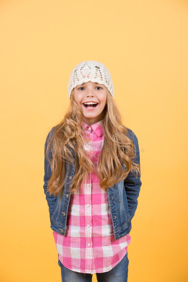 Fille dans le costume de jeans, chapeau, chemise de plaid sur le fond orange photo stock