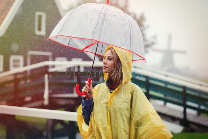 Fille dans le costume de pluie avec le séjour de parapluie sur le pont avec les moulins néerlandais photos libres de droits