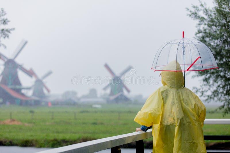Fille dans le costume de pluie avec le séjour de parapluie sur le pont avec les moulins néerlandais photos stock