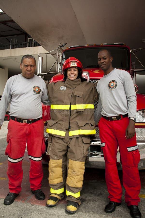 Fille dans le costume ignifuge avec 2 pompiers photo stock