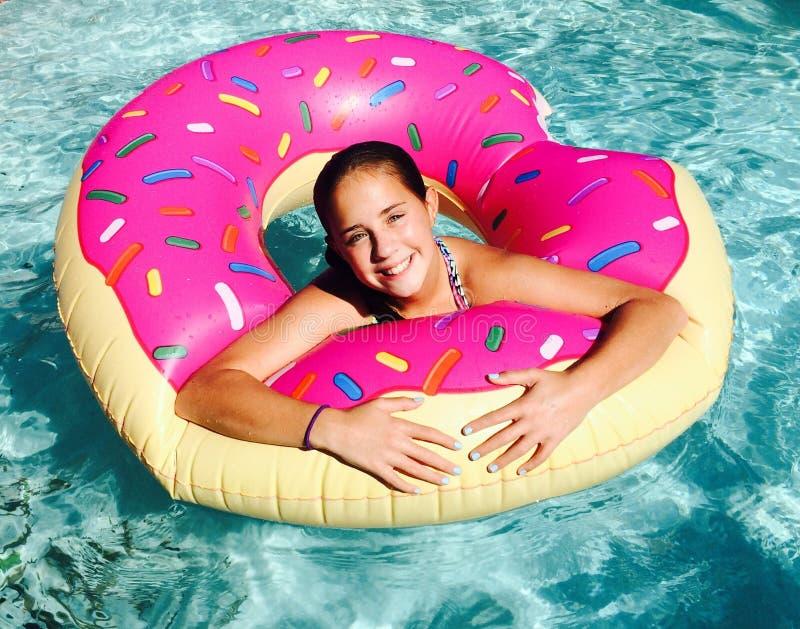 Fille dans le flotteur de beignet dans la piscine photographie stock libre de droits
