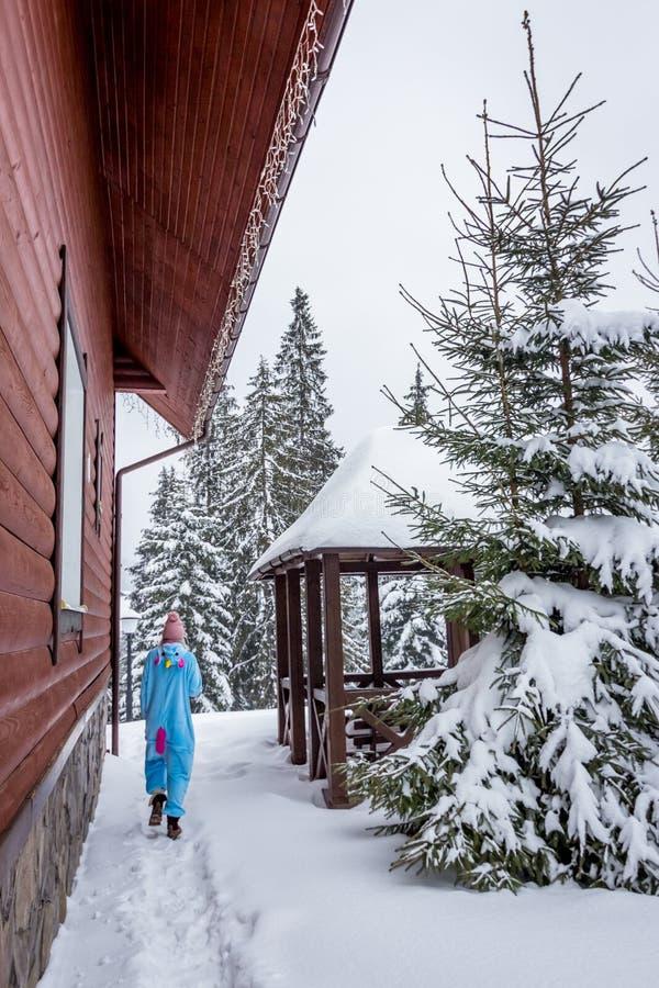 Fille dans le kigurumi bleu et rose de pijama de licorne extérieur devant les maisons en bois sur le rapport de ski en montagnes  photos stock