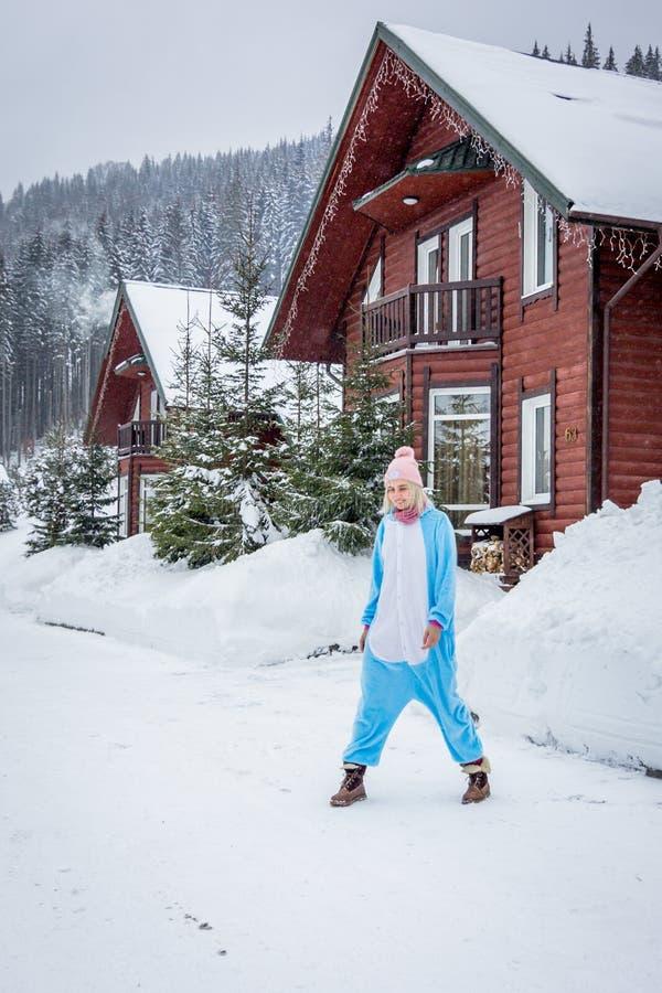 Fille dans le kigurumi bleu et rose de pijama de licorne extérieur devant les maisons en bois sur le rapport de ski en montagnes  photo libre de droits
