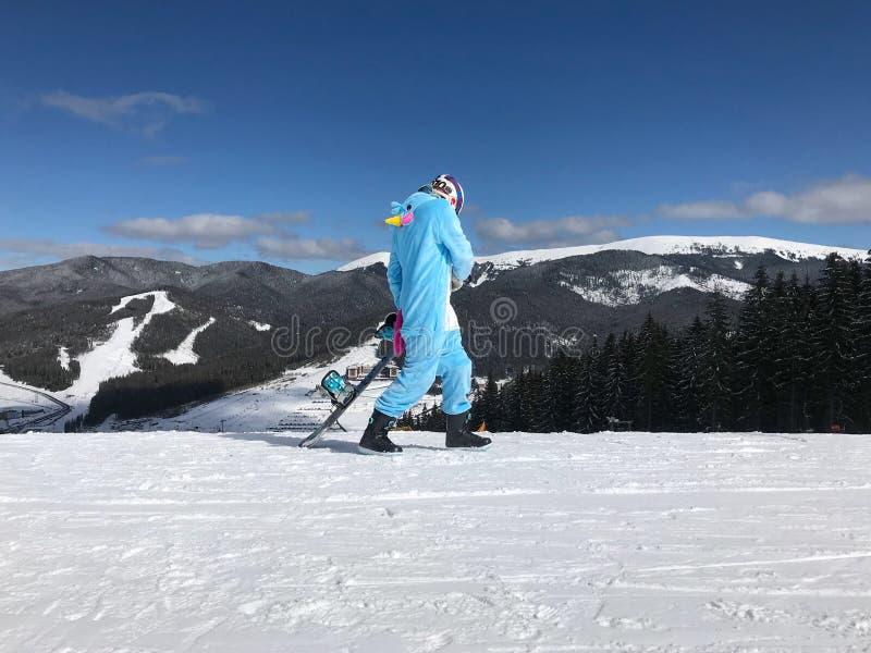 Fille dans le kigurumi bleu et rose de pyjama de licorne extérieur avec le surf des neiges sur le rapport de ski en montagnes de  image stock