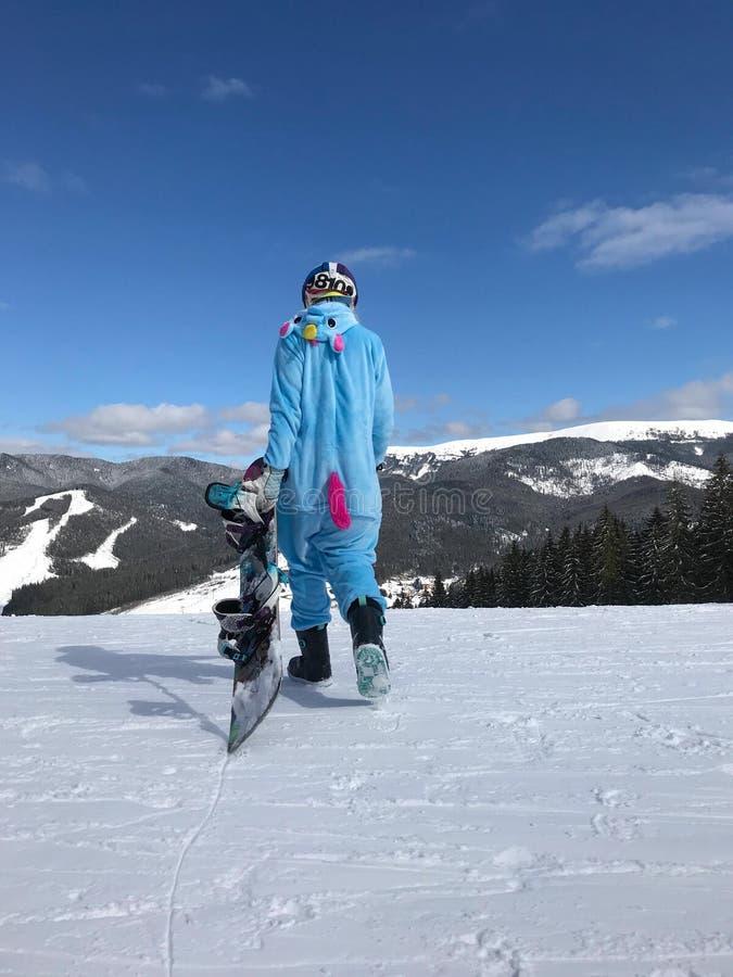 Fille dans le kigurumi bleu et rose de pyjama de licorne extérieur avec le surf des neiges sur le rapport de ski en montagnes de  photographie stock