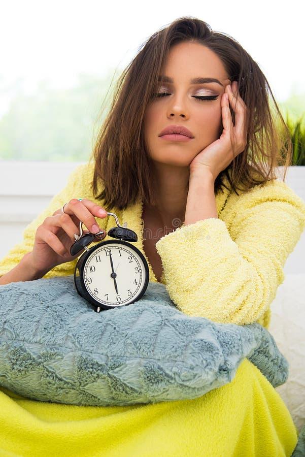 Fille dans le lit dans le matin avec la rétro horloge photo stock