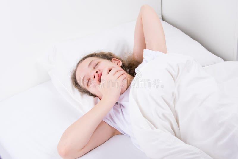 Fille dans le lit, sur un fond blanc, bâillements, bouche grande ouverte photos libres de droits