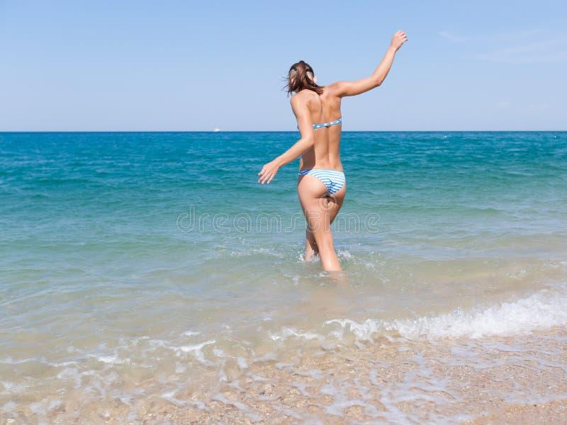 Fille dans le maillot de bain essayant de garder l'équilibre pour entrer dans la mer photographie stock libre de droits