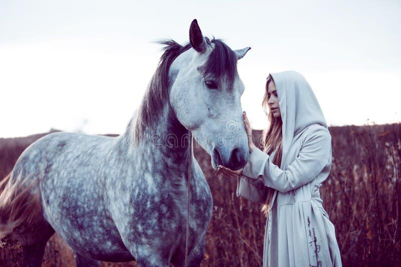 fille dans le manteau à capuchon avec le cheval, effet de la tonalité photographie stock libre de droits