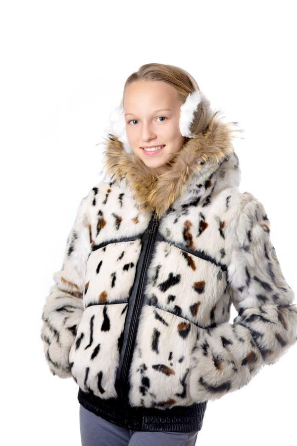 Fille dans le manteau d'hiver avec des bouche-oreilles photographie stock libre de droits