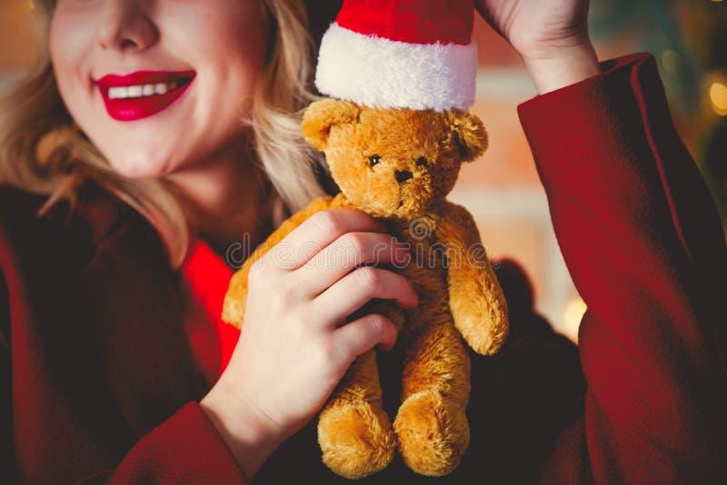 Fille dans le manteau rouge avec l'ours de nounours et le chapeau de Santa Claus images stock
