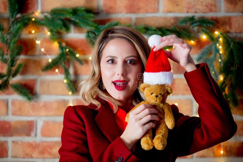 Fille dans le manteau rouge avec l'ours de nounours et le chapeau de Santa Claus photo stock