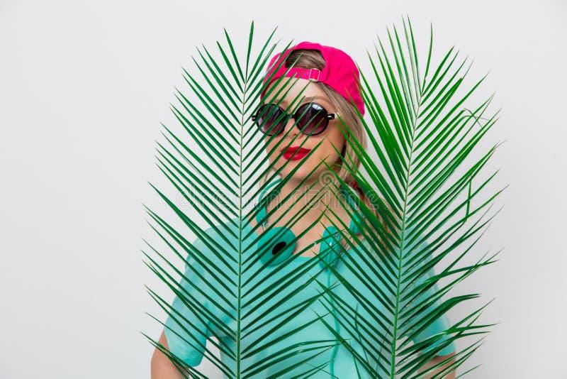Fille dans le T-shirt avec la branche verte de paume photos stock