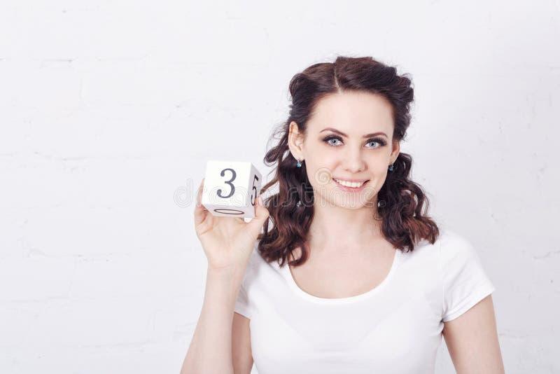 Fille dans le T-shirt blanc tenant le numéro trois photo stock