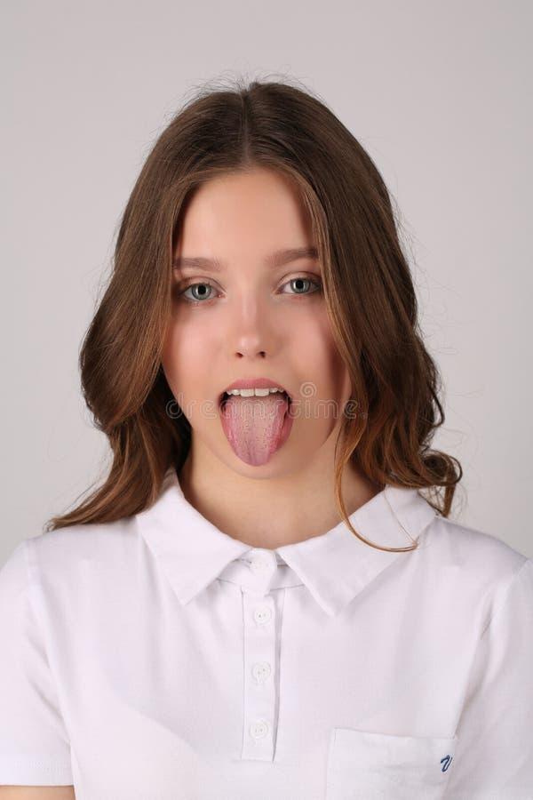 Fille dans le T-shirt montrant sa langue Fin vers le haut Fond blanc photo stock