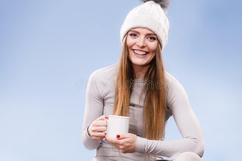 Fille dans le thé potable de sous-vêtements thermiques photos stock