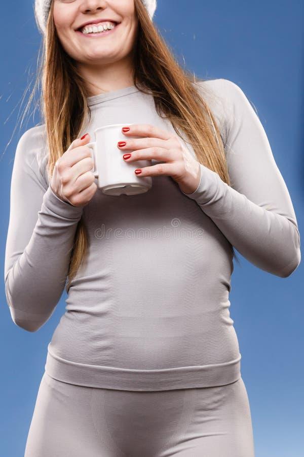 Fille dans le thé potable de sous-vêtements thermiques photographie stock libre de droits