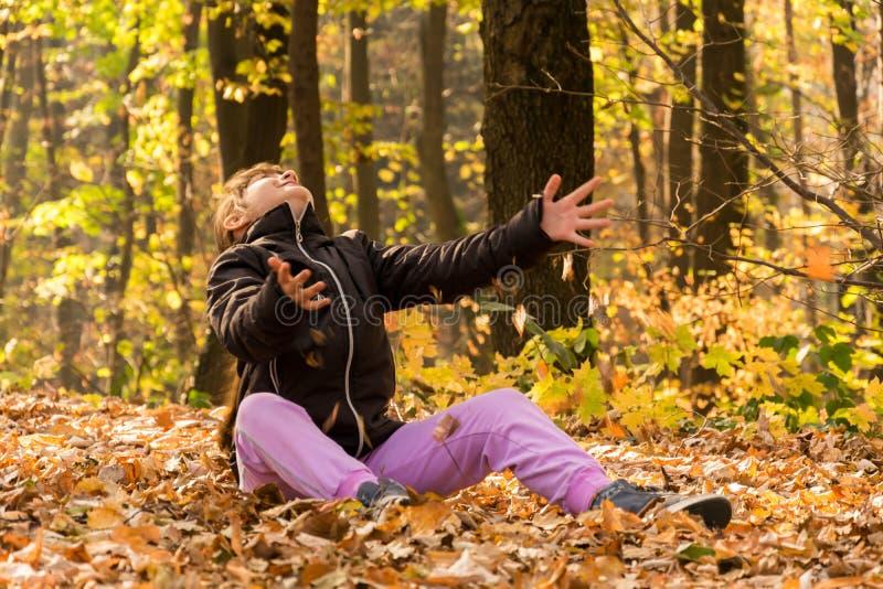 Fille dans les bois jouant avec les feuilles tombées photo stock