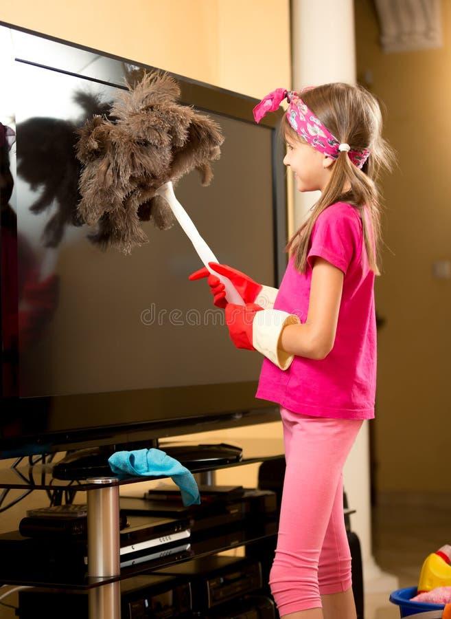 Fille dans les gants en caoutchouc nettoyant la grande TV de la poussière avec la brosse photographie stock libre de droits