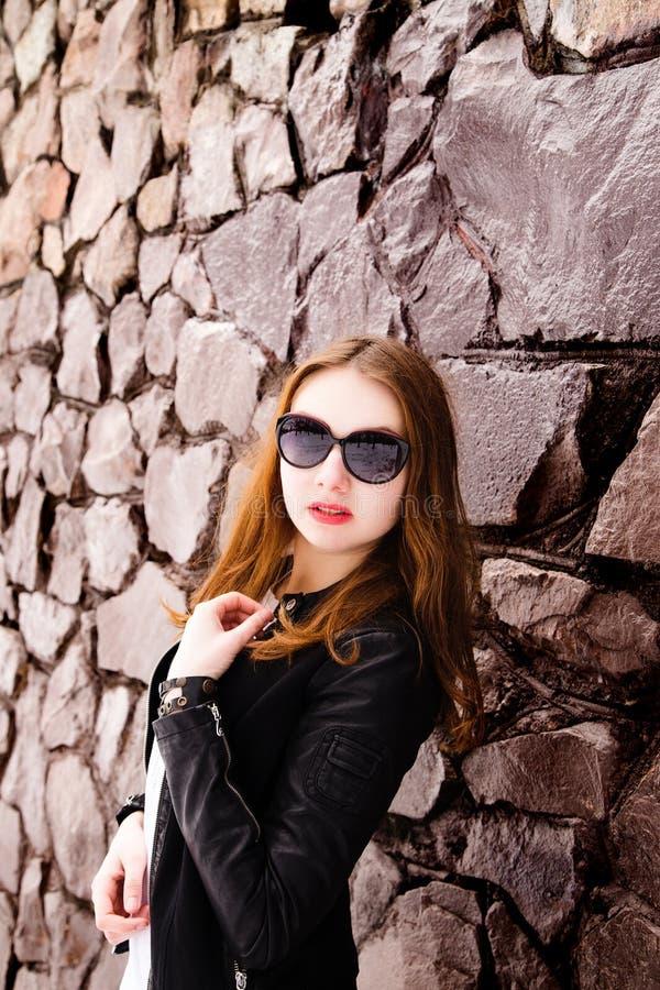 Fille dans les lunettes de soleil et la veste noires au-dessus d'un mur de briques images stock