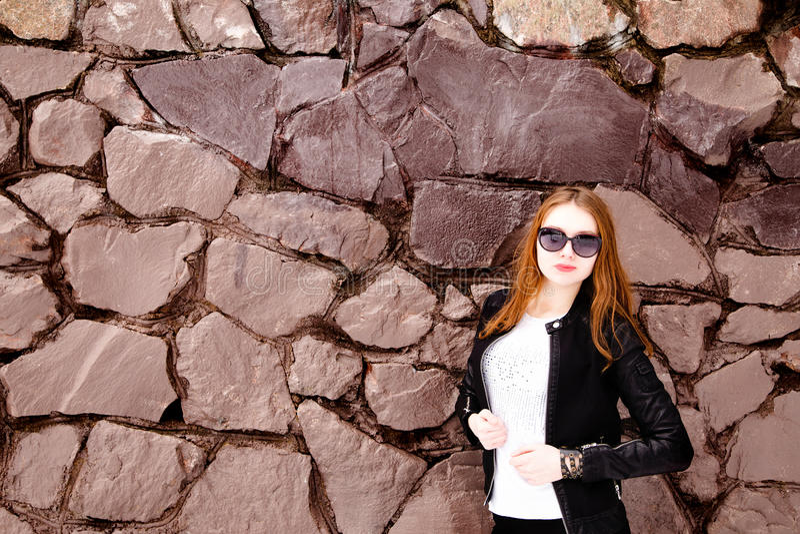 Fille dans les lunettes de soleil et la veste noires au-dessus d'un mur de briques photo stock