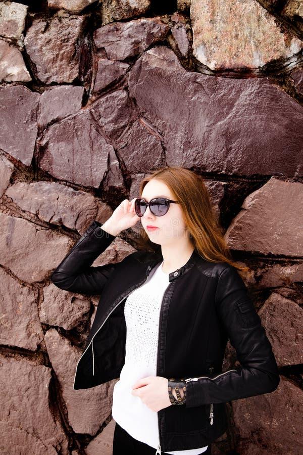 Fille dans les lunettes de soleil et la veste noires au-dessus d'un mur de briques photo libre de droits