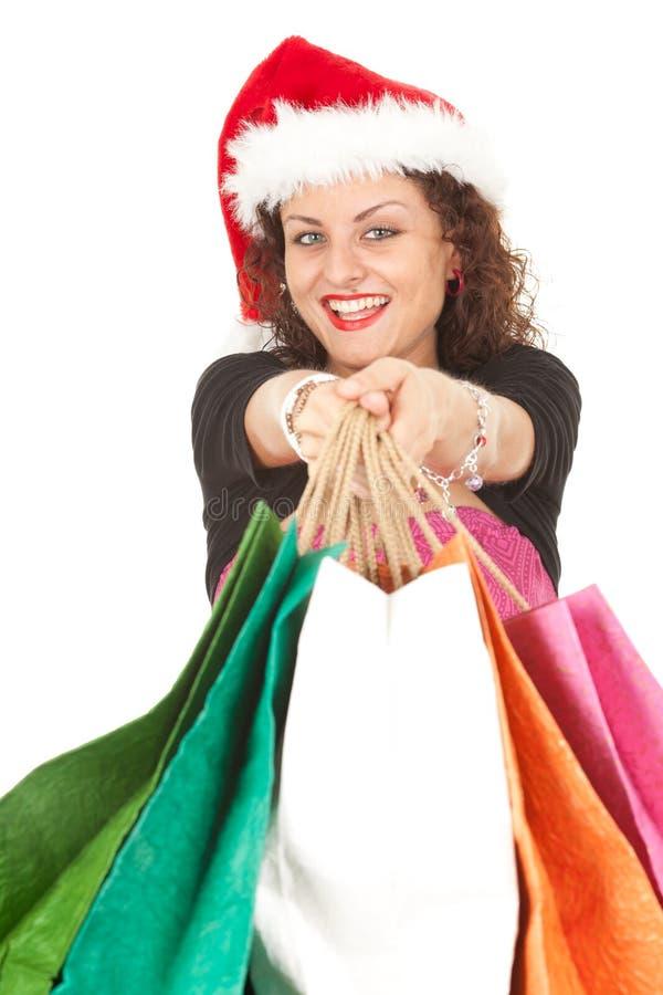 Fille dans les sacs à provisions de transport de chapeau de Santa photographie stock