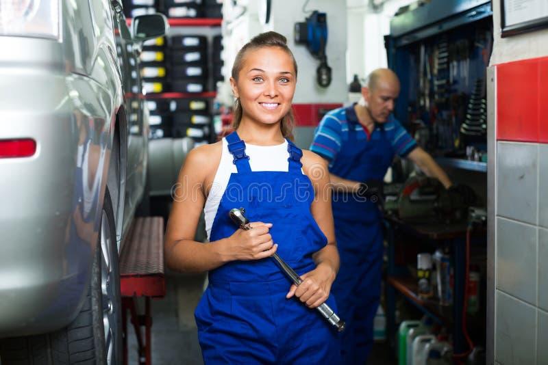 Fille dans les vêtements de travail dans l'atelier de mécanicien automobile photos libres de droits