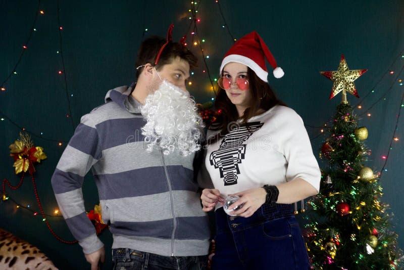 Fille dans les verres et le chapeau roses de Santa et un type avec une barbe blanche photo stock