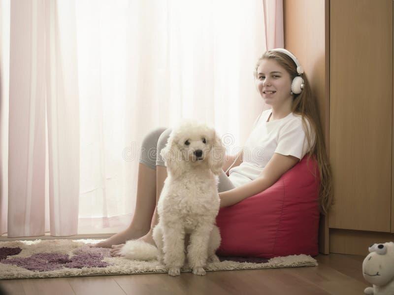 Fille dans sa chambre avec un chien images stock