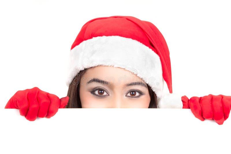 Fille dans Santa jetant un coup d'oeil au-dessus du panneau de signe photographie stock libre de droits