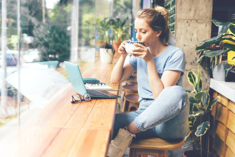 Fille dans un café avec un ordinateur portable photos libres de droits